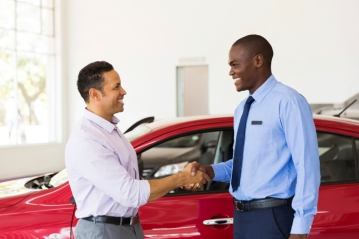 smiling african american car dealer handshake with customer